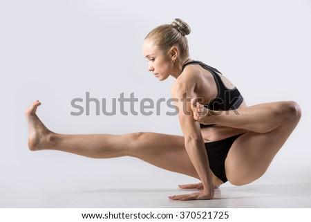 Sporty beautiful young woman practicing yoga, doing handstand asana Eka Pada Danda Brahmachariasana, working out wearing sportswear, studio, full length Strengthening abdominal muscles, thigh, arms - stock photo