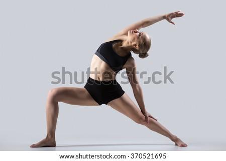 Sporty beautiful young woman practicing yoga, doing high lunge exercise, Reverse Warrior Pose, Viparita Virabhadrasana, working out wearing black sportswear, studio, full length - stock photo