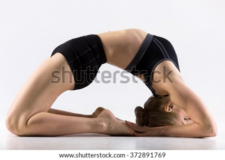 Sporty beautiful young woman practicing yoga, doing Pigeon Posture, Kapotasana, working out wearing black sportswear, stretching hip flexors, ankles, thighs and groins, abdomen and chest, studio