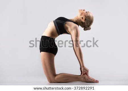Sporty beautiful young woman practicing yoga, doing Ushtrasana, Camel Pose, working out wearing black sportswear, studio, full length - stock photo