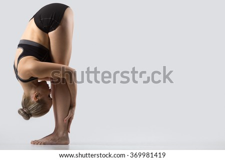 Sporty beautiful young woman practicing yoga, doing Uttanasana (intense stretch, Standing forward bend pose), working out wearing black sportswear, studio, full length, side view, copy space