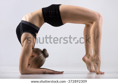 Sporty beautiful young woman practicing yoga, doing variation of Bridge Pose on elbows, standing in Urdhva Dhanurasana (Upward Bow), Chakrasana (Wheel), working out wearing black sportswear, studio - stock photo