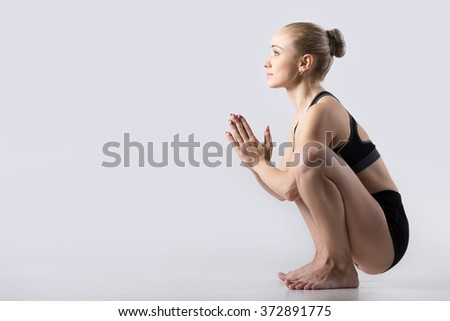 Sporty beautiful young woman practicing yoga, sitting in squat, Garland Pose, Malasana, stretching back muscles, hips, ankles, working out wearing black sportswear, studio - stock photo
