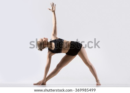 Sporty beautiful young woman practicing yoga, standing in Trikonasana pose, working out wearing black sportswear, studio full length, grey background