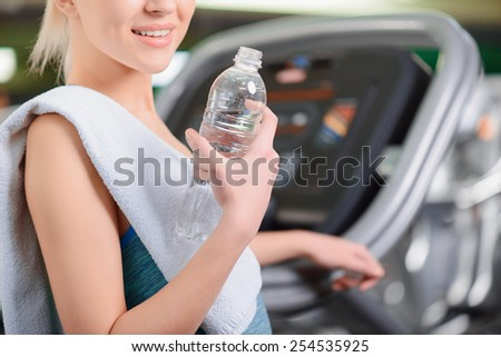 Sporty beauty. Cropped image of attractive young woman in sports clothing holding bottle with water and smiling while standing in health club - stock photo