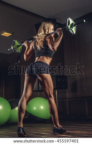 Sporty blond female from the back doing exercises with green barbell in a gym
