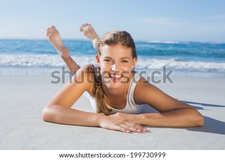 Sporty blonde lying on the beach smiling at camera on a sunny day - stock photo