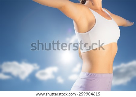 Sporty blonde standing on the beach with arms out against cloudy sky with sunshine - stock photo