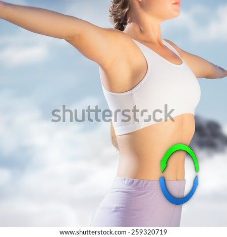 Sporty blonde standing on the beach with arms out against mountain peak through the clouds - stock photo