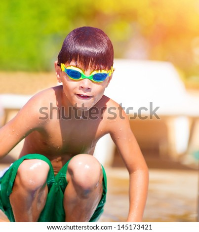 Sporty boy jumping into the pool, wearing swimmer goggles, active childhood, water sport, summer vacation, refreshment and joy concept - stock photo