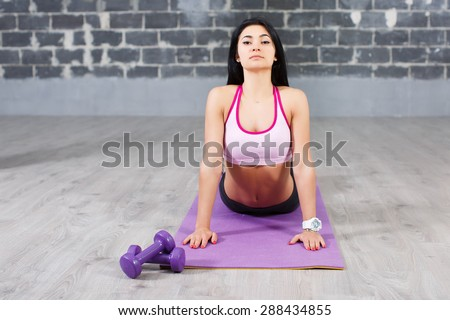 Sporty brunette girl doing exercises for flexible spine on brick wall background, yoga asana from Surya Namaskar sequence, Sun Salutation complex, urdhva mukha shvanasana (upward facing dog pose) - stock photo