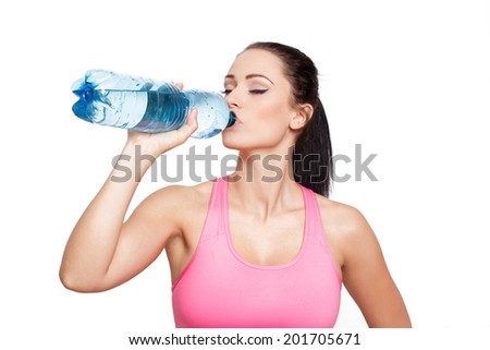 Sporty brunette woman drink water from bottle, isolated on white background - stock photo