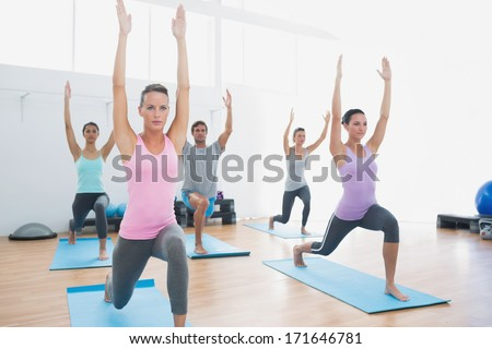 Sporty class doing pilate exercises in the fitness studio - stock photo