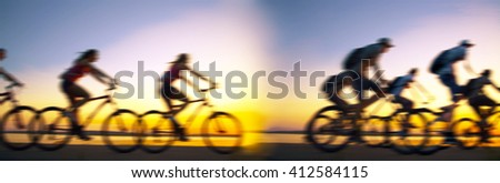 Sporty company friends on bicycles outdoors against sunset Silhouette eight 8 cyclist going along shoreline coast Reflection sun on water Sport in Nature background Group of people. Empty Copy Space  - stock photo