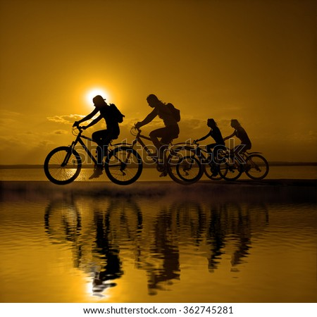 Sporty company friends on bicycles outdoors against sunset Silhouette 4 four cyclist going along shoreline coast Reflection sun on water Sport in Nature background Group of people. Empty Copy Space