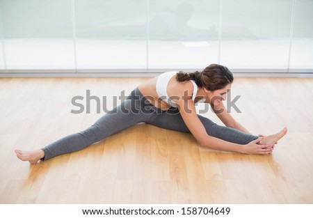 Sporty content brunette stretching on the floor in bright room