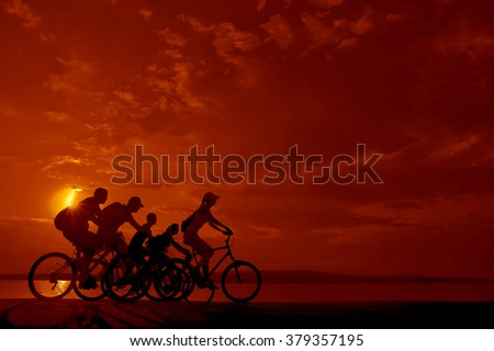 sporty couple friends on bicycles outdoors against sunset. Silhouette of motion go of five 5 cyclist along shoreline coast Reflection sun on water. Empty Copy Space for inscription, people or objects