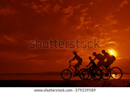 sporty couple friends on bicycles outdoors against sunset. Silhouette of motion go of four 4 cyclist along shoreline coast Reflection sun on water. Empty Copy Space for inscription, people or objects