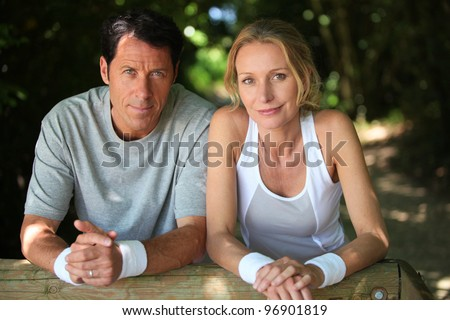Sporty couple having a rest from exercise in the country - stock photo