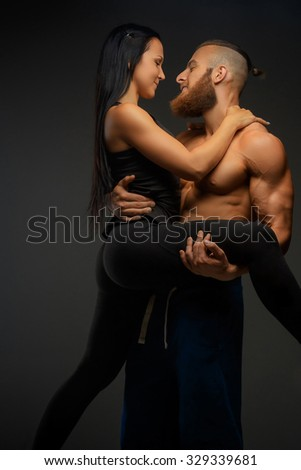 Sporty couple. Shirtless muscular man holding on arms his athletic woman.