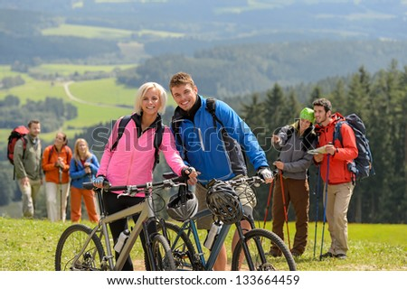 Sporty cyclist couple and hikers posing during springtime weekend - stock photo