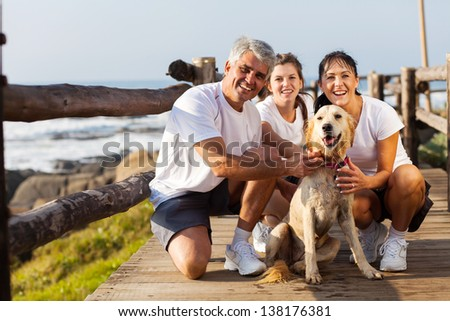 sporty family and their pet dog at the beach in the morning - stock photo