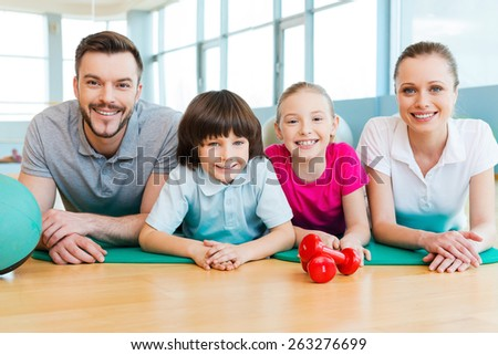 Sporty family. Happy sporty family bonding to each other while lying on exercise mat together   - stock photo