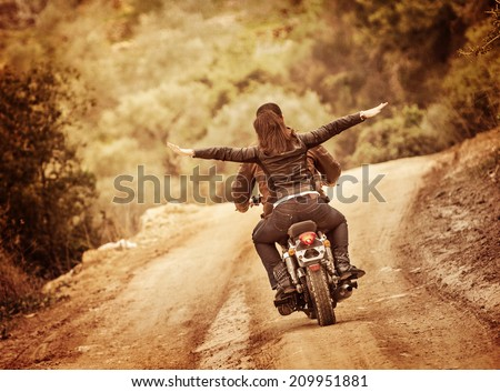 Sporty family traveling on motorbike, riding on motorcycle with raised up hands, active people, extreme sport, freedom concept - stock photo