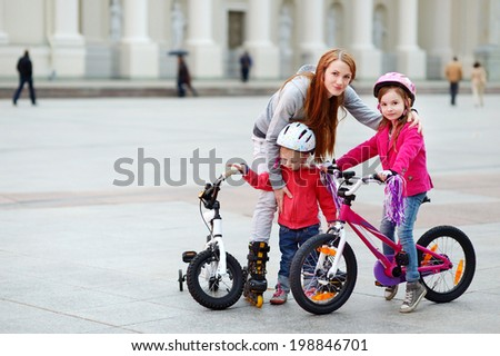 Sporty family - young mother with kids in a city - stock photo