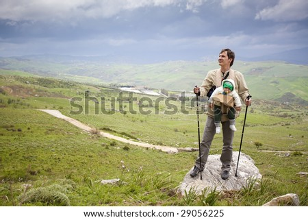 sporty father climbing mountains with his baby son - stock photo