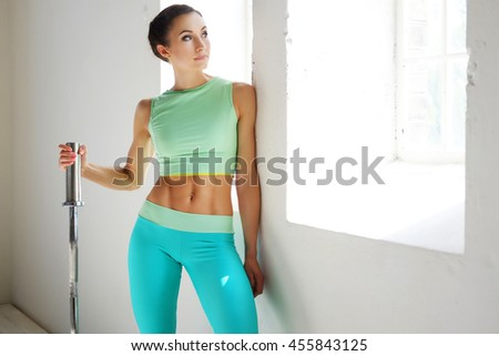 Sporty female posing with barbell griff near window in natural light.