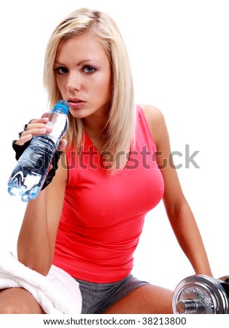 Sporty female sitting in the gym with bottle of water in hands