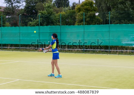 Sporty female tennis player wearing a sportswear warming up before tennis match on a court outdoor in summer or spring