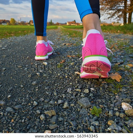 Sporty female walking and running on a road - stock photo