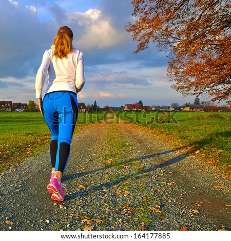 Sporty female walking and running on autumn road - stock photo