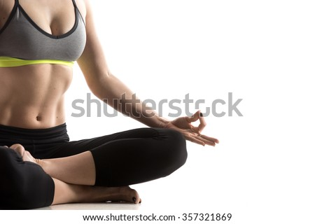 Sporty fit beautiful young woman in sportswear bra and black pants working out, sitting in Fire Log pose, Square Posture for hips and groins, studio close-up, isolated, white background - stock photo