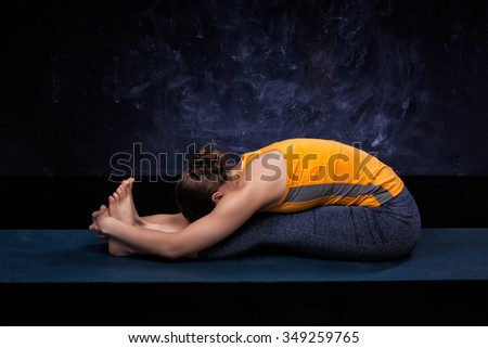 Sporty fit woman practices Ashtanga Vinyasa yoga back bending asana Paschimottanasana - seated forward bend - stock photo