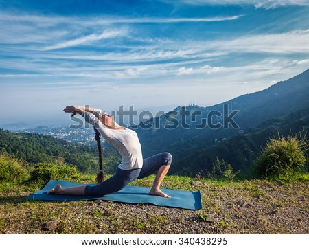 Sporty fit woman practices yoga Anjaneyasana - low crescent lunge pose outdoors in mountains in morning - stock photo