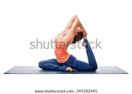Sporty fit yogini woman doing yoga asana Eka pada kapotasana - one-legged pigeon pose isolated on white - stock photo