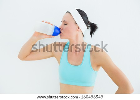 Sporty fit young woman drinking water over white background - stock photo