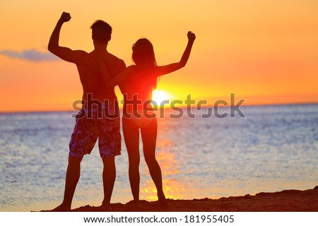 Sporty fitness couple cheering at beach sunset. Happy romantic fit young couple enjoying sunset with arms raised up flexing muscles together. People on sports vacation getaway. - stock photo