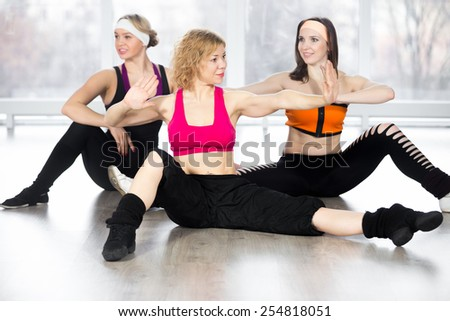 Sporty fitness instructor conducts aerobics training, group of three smiling women doing dynamic sport exercises with choreographic elements in class - stock photo
