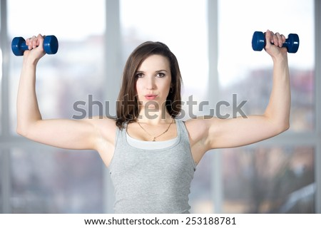 Sporty girl athlete leading active lifestyle, doing fitness training for biceps in grey sportswear with dumbbells, lifting weights, warming up, breathing, exhaling, exhausted - stock photo