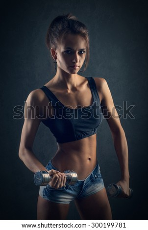 sporty girl doing exercise with dumbbells - stock photo