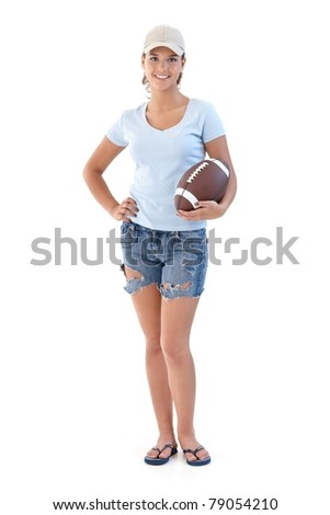 Sporty girl holding American football, smiling, looking at camera.? - stock photo