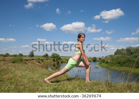 Sporty girl in green exercising on meadow against the sky
