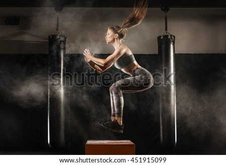 sporty girl jumping over some boxes in a cross-training gym - stock photo
