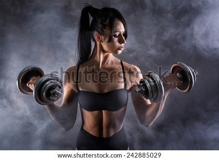 Sporty girl posing with dumbbells in the fog - stock photo