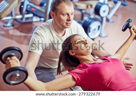 Sporty girl training in gym with her trainer helping her - stock photo