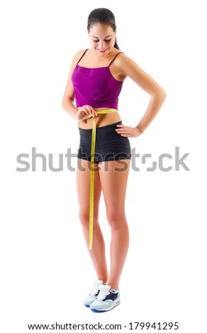 Sporty girl with measurement tape isolated - stock photo
